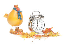 Fall Back DayLight Savings Side View. A side close-up view studio shot of a silver alarm clock with a plastic hen and fall leaves Royalty Free Stock Image