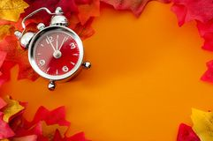 Fall back, the end of daylight savings time and turn clocks back on hour concept with a clock surrounded by dried yellow leaves. With the copy space for text stock photo