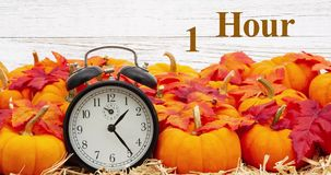Fall Back 1 hour time change message with a retro alarm clock with pumpkins and fall leaves