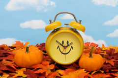 Fall Back Time Change. Fall leaves with yellow clock and pumpkins on sky background, fall back time change Royalty Free Stock Photography