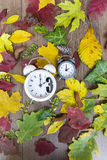 Fall Back Time Change.Two clocks on autumn leaves background Royalty Free Stock Photography