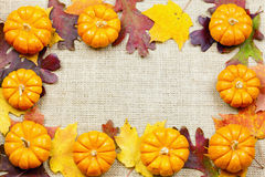 Fall background. Fall-themed background of burlap, dry leaves and pumpkins Stock Image