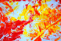 Fall background. A colorful abstract fall background of red and yellow leaf prints blueish material Stock Photo