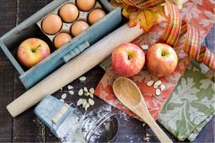 Fall Baking with Apples. A rustic scene with apples, almonds, flour, rolling pin, fall colors and all the warm colors of the season royalty free stock images