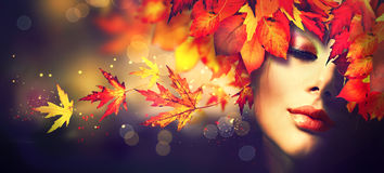 Fall. Beauty girl with colourful autumn leaves hairstyle royalty free stock images