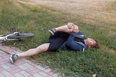 Fall from bike in natural park. Young caucasian man fell off the bicycle on the ground. Accident with a stick in a wheel. stock photography