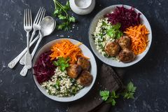 Fall buddha bowl. Bulgur, spinach, meatballs, beets, carrots - balanced healthy eating lunch. On a dark background, top view. stock image