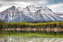 Fall in the Canadian Rockies. A dusting of snow on the tall rocky mountain peaks and reflection on a calm lake. this scene was captured in Banff National Park stock images