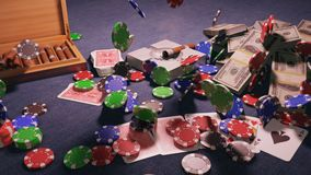 The fall of casino chips on the poker table in the casino. A gentleman`s set, a Smoking cigar, cards, chips and wads of