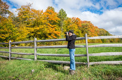 Fall color in the Adirondacks. Woman taking a photograph of the fall color in the Adirondacks Royalty Free Stock Photography