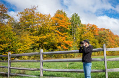 Fall color in the Adirondacks. Woman taking a photograph of the fall color in the Adirondacks Stock Photos