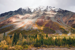 Fall Color Snow Capped Peak Alaska Range Fall Autumn Season. The sun peeps through a partly cloudy sky to light the Alaska Range Royalty Free Stock Images