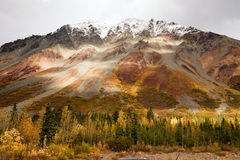 Fall Color Snow Capped Peak Alaska Range Fall Autumn Season. The sun peeps through a partly cloudy sky to light the Alaska Range Stock Photo