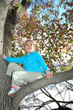 Fall Colors. An eight year old girl climbs up in a tree. A girl exploring and having fun outside in nature. Happy child in a tree Royalty Free Stock Photography