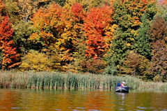 Fall colors. Beautiful fall colors make a background for a fishing scene Royalty Free Stock Photos