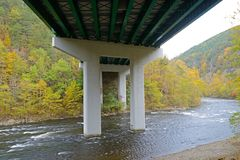 Fall colors along a lazy river in the Smokies. Underneath a concrete bridge along the river in fall colors stock image