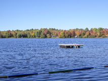 Fall colors in cottage country. Lake with autumn leaves and dock royalty free stock photo