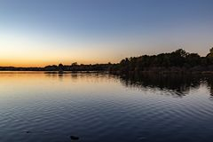 Fall colors at dusk with ripples on the lake. Colorful skyline royalty free stock photo