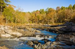 Fall colors at the Cossatot River. Fall colors frame the background of the Cossatot River in November royalty free stock photo