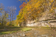 Fall Colors and a Limestone Cliff over a Quiet Stream. stock photos