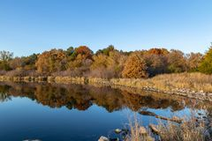 Fall colors in a park with reflections in the lake in Omaha Nebraska. View of fall colors in a park at sunset with reflections in the lake in Omaha Nebraska stock image