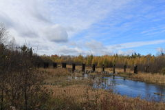 Autumn scenery competes with view of beautiful cloudy sky and ruins of abandoned bridge reflected in a river in Hayward, Wisconsin Stock Photography
