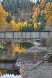 Fall Colors Reflectons and a Railroad Bridge. The Fall colors are reflected in a small creek, spanned by an railroad bridge, along picturesque Highway 10 between stock images