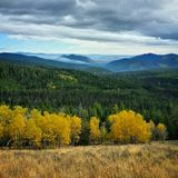 Fall colors with smoke. Golden colored trees in the fall overlooking Conconully and the smoke from a prescribed forest fire burn in the distant mountains royalty free stock photography
