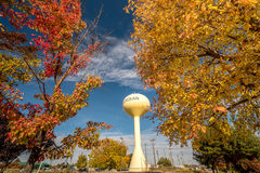 Fall colors souround yellow Meridian water tower Royalty Free Stock Images