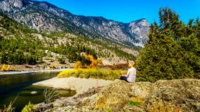 Fall colors by the Thompson River in BC Canada. Senior Woman enjoying the Fall colors by the Thompson River at Goldpan Provincial Park, on the Fraser Canyon royalty free stock photo