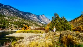 Fall colors by the Thompson River in BC Canada. Senior Woman enjoying the Fall colors by the Thompson River at Goldpan Provincial Park, on the Fraser Canyon royalty free stock photography