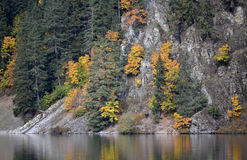 Fall Colours. Colourful trees along a mountain shoreline on a lake Stock Photos