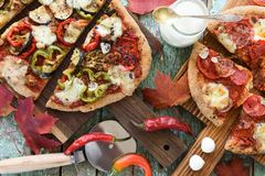 Fall comfort meal. Homemade pizzas with eggplants, peppers, sala royalty free stock photo