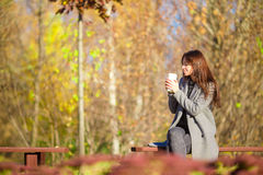 Fall concept - beautiful woman drinking coffee in autumn park  under fall foliage Stock Photo