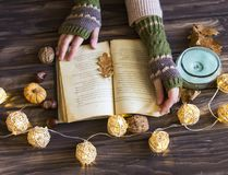 Fall concept reading, woman hands with an open book, dried leave. Autumn concept reading, woman hands with an open book, dried leaves and candle, top view Royalty Free Stock Images