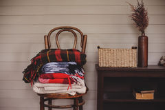 Fall at country house. Seasonal rustic decorations with cozy blankets and flowers. On wooden background on chair Royalty Free Stock Photo