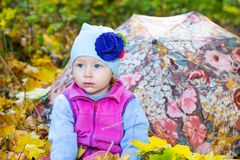 Fall. Cute child girl playing with fallen leaves in autumn Stock Image
