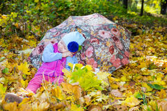 Fall. Cute child girl playing with fallen leaves in autumn Stock Photo