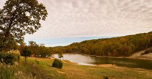 Cloudy Sky by a stream in the Ozarks mountains of Missouri. Fall day with the colored leaves outdoors in the Ozark Mountains of Missouri royalty free stock photography