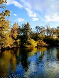 Fall Day on the Huron River in Ann Arbor Michigan. Fall day on river reflection of trees fall colors sky clouds stock photography