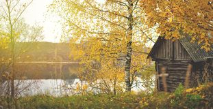 Fall days. Wooden hous near by river. Colorful autumn stock photo