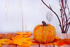 Fall decorations. A decorative pumpkin and fall leaves with bare branches on wood rustic background stock photo
