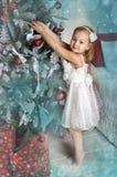 Fall des kleinen Mädchens auf dem Weihnachtsbaum spielt Lizenzfreie Stockfotografie