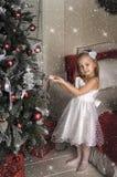 Fall des kleinen Mädchens auf dem Weihnachtsbaum spielt Stockfoto