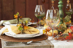 Fall dining place settings on rustic table and wall
