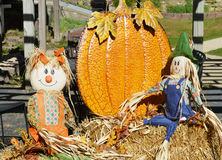 Fall Display. A fall display of scarecrows and a large pumpkin on straw, hay bales.  The girl scarecrow is wearing orange overalls and bows in her hair and the Stock Images