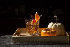 Fall Drinks - Old Fashioned Whiskey Cocktail. Closeup of Old Fashioned Whiskey Cocktail at a bar ready to be served. Mini pumpkins and cinnamon sticks. Fall royalty free stock images