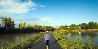 Fall Exercise. Woman walking her black labrador retriever along a path next to the Erie Canal, Rochester, New York during autumn Stock Image
