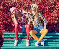 Fall Fashion. Urban Outdoor.Woman Sitting on Steps. Urban Outdoor. Fall Fashion. Hipster Friends Sitting on Bench, Relax Enjoy Nature. Fashion. Cheeky Model Girl Royalty Free Stock Photos