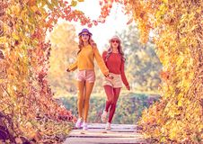 Fall Fashion. Urban Outdoor. Woman Walking in Park. Fall Fashion. Two Young Woman Jumping Having Fun in Autumn Park. Urban Outdoor. Adorable Girl Sisters Happy Royalty Free Stock Images